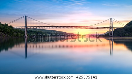 Bear Mountain Bridge at sunrise (long exposure). Bear Mountain Bridge is a toll suspension bridge in New York State, carrying U.S. Highways 202 and 6 across the Hudson River #425395141