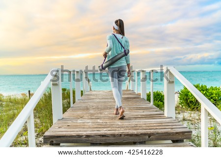 Fitness woman walking with yoga mat on beach going to outdoor meditation class at sunset. Back view of fit athlete in activewear fashion leggings and turquoise hoodie. Healthy active lifestyle. #425416228