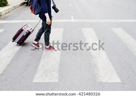 Tourist with suitcase walking in the city #425480326