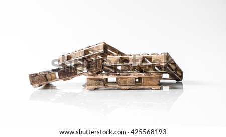 Mix stack of miniature wooden pallet. Concept of shipping and logistics. Isolated on white background. Slightly de-focused and close-up shot. Copy space. #425568193