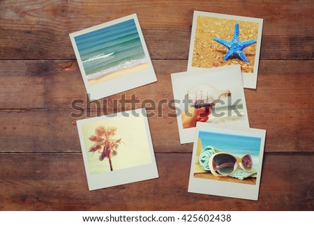 top view of instant photos album on wooden background. vintage filtered image