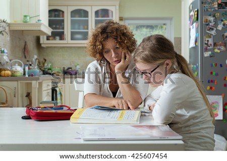 Mother helping daughter with her homework at the table in the dining room.  #425607454