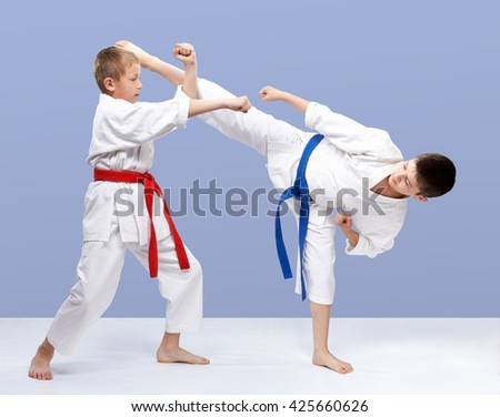 With red and blue belt boys are training strikes and blocks #425660626