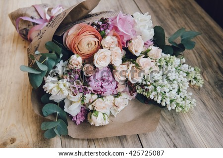 Beautiful flower bouquet of fresh white lilac, roses, ranunculus, peony, hyacinth, eucalyptus on the wooden rustic table Royalty-Free Stock Photo #425725087