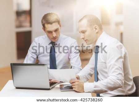 business, technology and office concept - two businessmen with laptop, tablet pc computer and papers having discussion in office #425738260