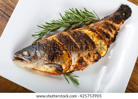 Hot fresh grilled trout with lemon and rosemary #425753905