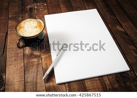 Blank branding template on vintage wooden table background. Letterhead, coffee cup and pen. Photo of blank stationery. Mock-up for design portfolios. Royalty-Free Stock Photo #425867515