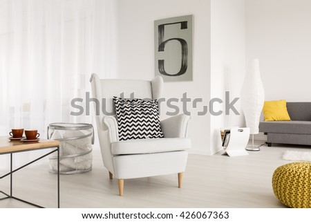 Light living room with simple table and comfortable armchair with decorative pattern pillow #426067363