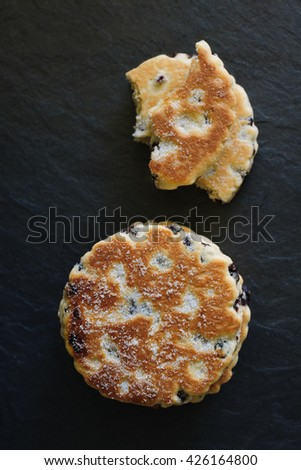 Welsh cakes or Pic ar y maen a traditional griddle cake made with flour and dried fruit on a slate background top down view