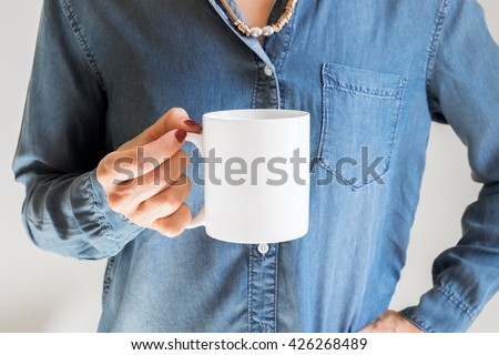 Hand holding a white coffee cup on denim shirt background. Mock up, perfect for putting your design on. #426268489