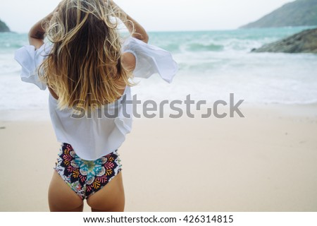 watching the coming sea storm - beautiful woman standing  on the beach. Blond hair with ombre coloring. Hipster toning. Soft focus.