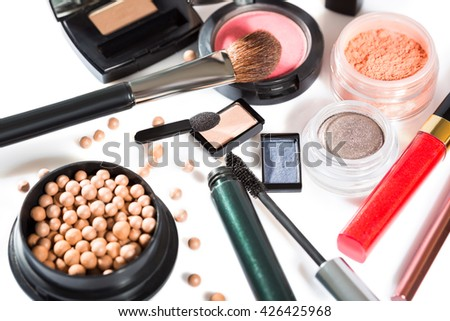 Diverse selection of brushes along side makeup powders, eye shadow, red and pink lipsticks and compact with foundation #426425968