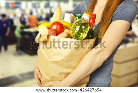 Basket with produce in woman hand on background from supermarket #426427654