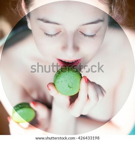 Beautiful naked woman eating green macaroons  #426433198