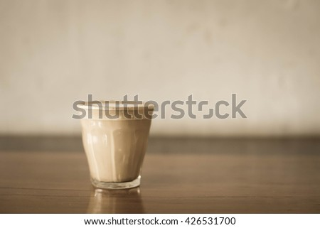 coffee cup and coffee beans.Coffee cup and coffee beans on a wooden table and sack background,Vintage color tone #426531700