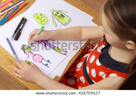 Girl in red dress draws a picture of the family. children's fears, bad dreams, nightmares.