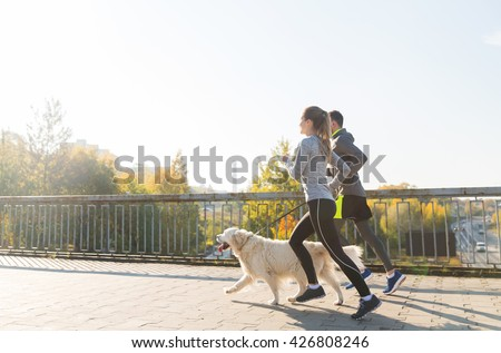 fitness, sport, people and jogging concept - happy couple with dog running outdoors #426808246
