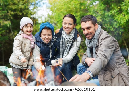 camping, travel, tourism, hike and people concept - happy family roasting marshmallow over campfire #426810151