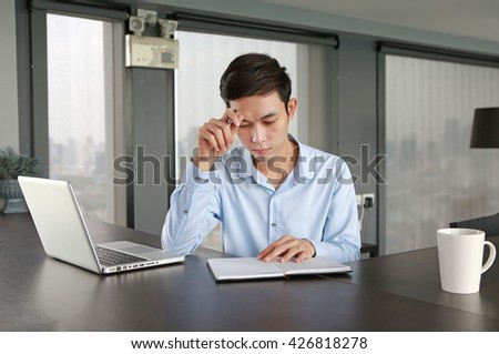 Young businessman sitting at the table on workplace in office is thinking #426818278