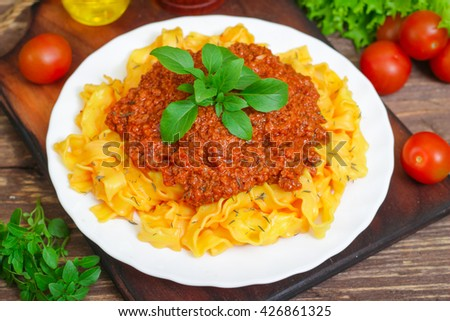 Traditional Italian pasta Bolognese or Bolognese with cooked pasta noodles topped with a spicy tomato based meat sauce garnished with fresh basil on a wooden background #426861325
