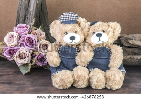 Two teddy bears holding hand and take a photo in studio over  bouquet of roses and timber background, love and friendship concept