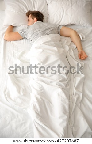 Young man sleeping alone in white big bed #427207687