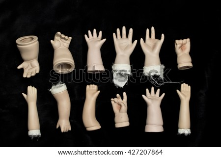 Broken Doll Body Parts on Black Background