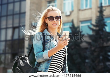 Young woman listening to music and walking along the street #427215466