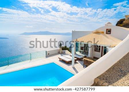 SANTORINI ISLAND, GREECE - MAY 24, 2015: A view of caldera with luxury house and pool in foreground, typical white architecture of Imerovigli village on Santorini island, Greece. #427587799