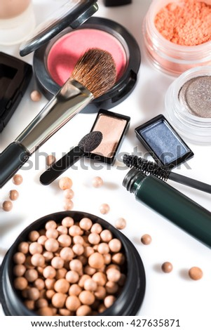 Diverse selection of brushes along side makeup powders, eye shadow, red and pink lipsticks and compact with foundation #427635871