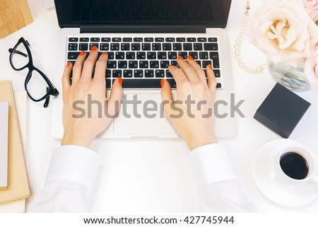 Topview of designer desktop with flowers, coffee, glasses and female hands typing on computer keyboard #427745944