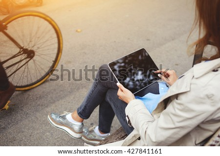 Rear view of young hipster girl is using portable touch pad for playing games, while is waiting car on a bus stop. Closeup image of stylish woman is holding digital tablet with copy space on screen