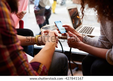 Closely image of woman is making an on-line purchase via cell telephone, while is sitting with friends in hipster cafe interior. Young female is reading information on web page via her mobile phone #427841167