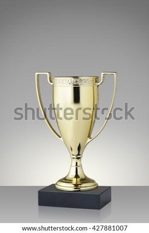 Golden trophy cup on gray background #427881007