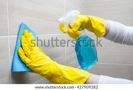 Housemaid cleaning a bathroom, closeup shot #427909282