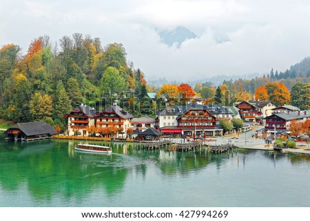 A sightseeing boat cruising on Konigssee ( King's Lake ) surrounded by colorful autumn trees and boathouses on a foggy misty morning~ Beautiful scenery of Bavarian countryside in Berchtesgaden Germany #427994269