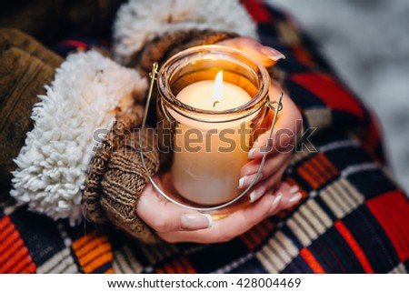 Female hands in warm winter closing holding a white burning candle in a glass #428004469