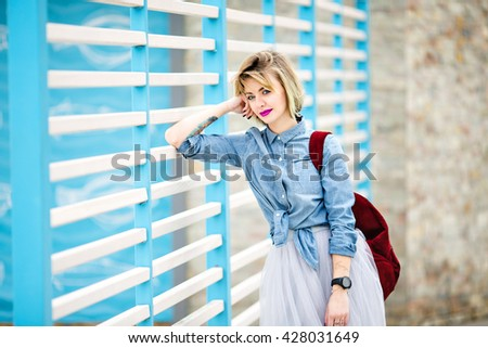 Portrait of a standing smiling girl with blond hair, bright pink lips and nude make up leaning on blue and white stripes fence on the background and wearing blue denim shirt,grey skirt and black watch #428031649