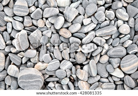 Heap of grey dry round stones background, top view.