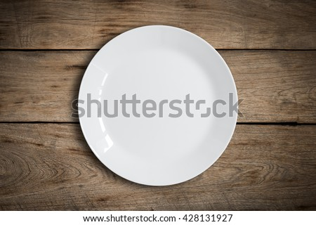Blank white dish on a wood background. Royalty-Free Stock Photo #428131927