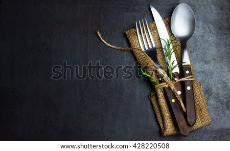 Rustic vintage set of cutlery knife, spoon, fork. Black background. Top view Royalty-Free Stock Photo #428220508
