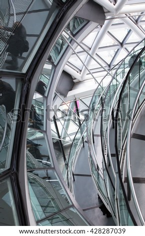 LONDON, UK - SEPTEMBER 19, 2016: Famous spiral staircases of London City Hall with walking people. Modern architectural structure  #428287039