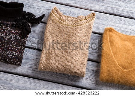 Different color sweatshirts. Folded sweaters on wooden background. Lady's brand new beige pullover. Dress warmly and stylishly. #428323222