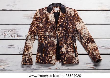 Girl's leopard blazer. Leopard blazer on wooden background. Exclusive garment from boutique. Luxury and originality. #428324020