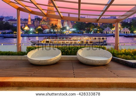 Relax corner on condominium rooftop garden with chairs on landmark bangkok Wat Arun and cruise ship in night background, Landmark concept