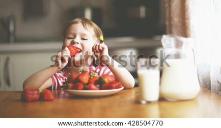 happy child girl drinks milk and eats strawberries in the summer home kitchen #428504770