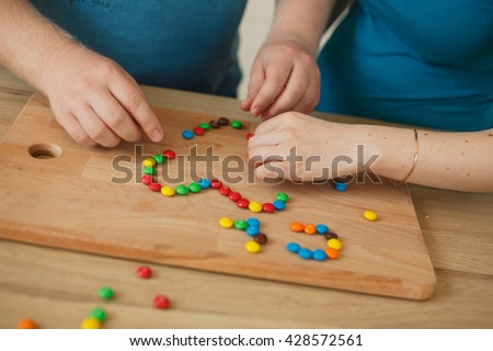 romantic couple holding a cutting board. The board is laid out candy mm heart symbol sign #428572561