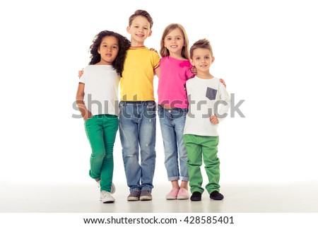Cute little kids in casual clothes are looking at camera and smiling while standing with their arms around each other, isolated on a white background