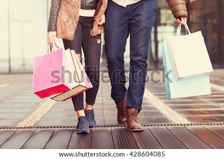Midsection of couple with shopping bags in city #428604085