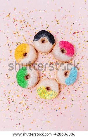 Stack of assorted donuts on a pink background #428636386